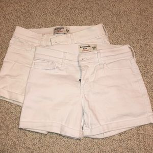 Two pairs of girls Abercrombie white jean shorts